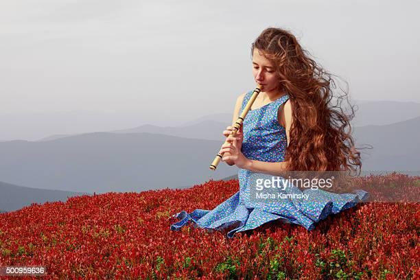 Giovane donna che suona il flauto in montagne