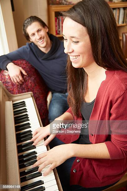 Young woman playing the piano for boyfriend