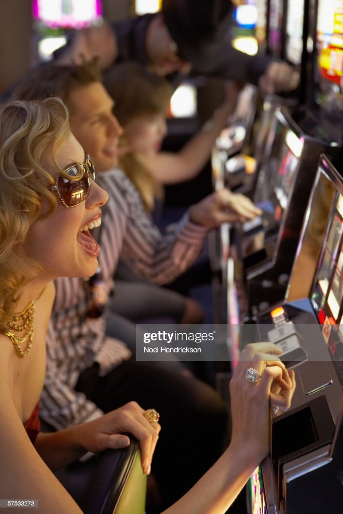 Young woman playing the slot machines in a casino : Stock Photo