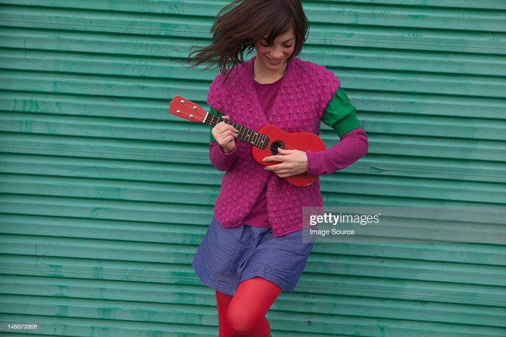 Young woman playing ukulele : Stock Photo