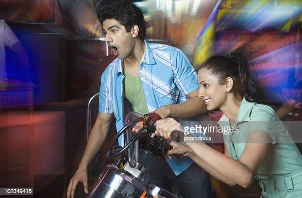 Young woman playing video game and a young man watching her game in a video arcade