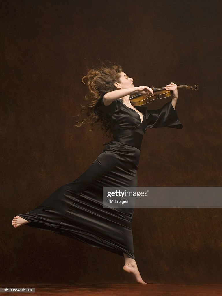 Young woman playing violin and jumping, side view