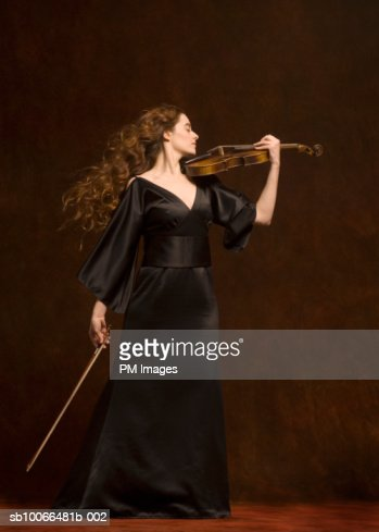 Young woman playing violin, eyes closed, side view