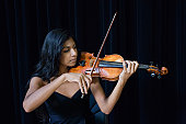 Young woman playing violin on stage, close-up