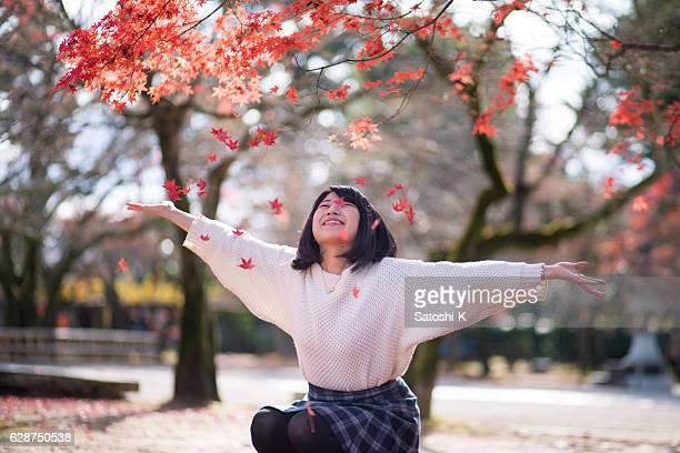 若い女性が、秋の葉