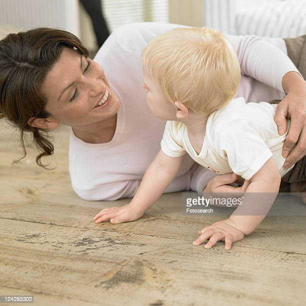Young woman playing with baby boy (0-6 months)