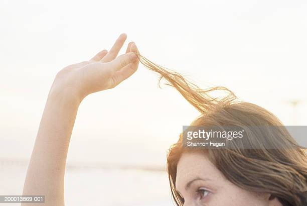 Young woman playing with hair, close up