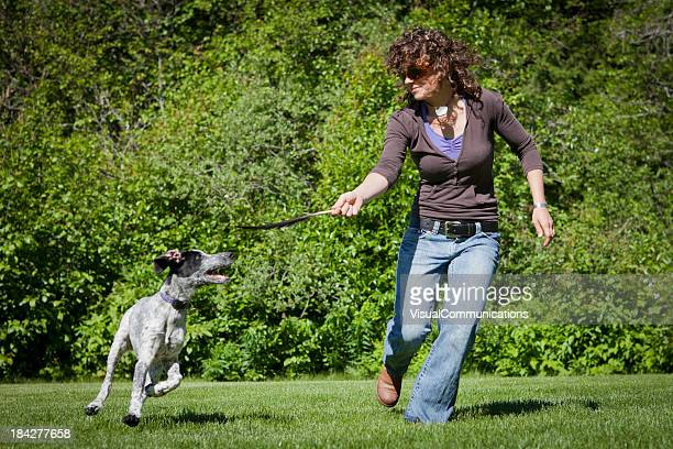 young woman playing with her dog in park.