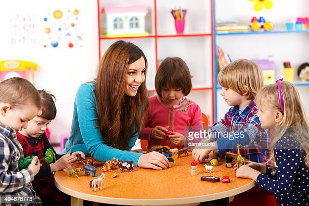 Young woman playing with kids in nursery school