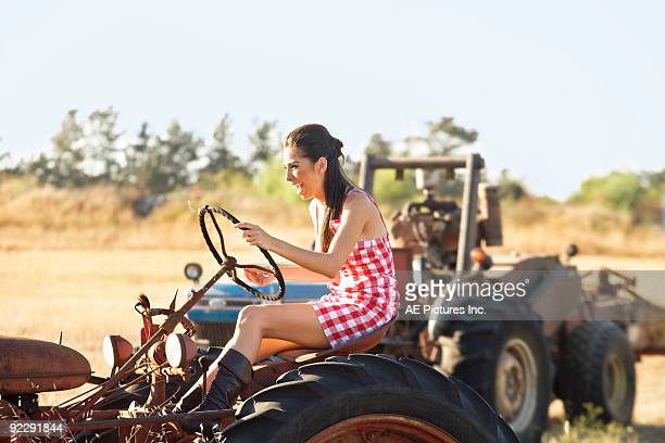 Young woman plays on vintage tractor