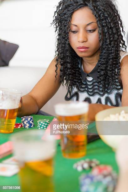 Young woman Plays Poker at home with friends