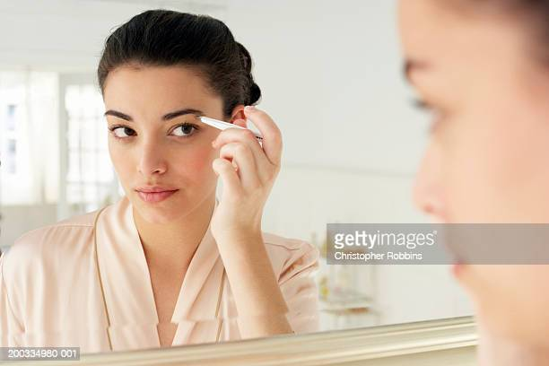 Young woman plucking eyebrows, close-up, reflection in mirror