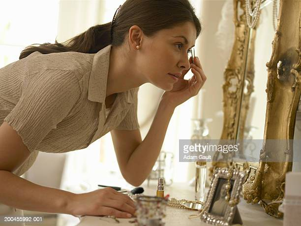 Young woman plucking eyebrows in mirror