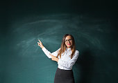 Businesswoman is pointing, looking at camera and smiling, standing against blackboard