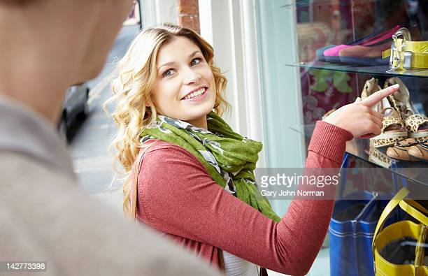 Young woman pointing at window display in boutique