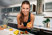 Young lady in sports wear standing at kitchen table with various fruits. Young cheerful lady in kitchen preparing fruit salad.