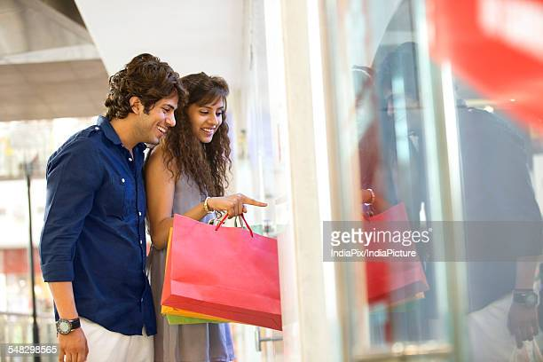 Young woman pointing with smiling man at shopping mall