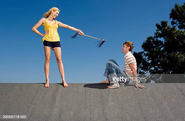 Young woman pointing with stick at young man on rooftop
