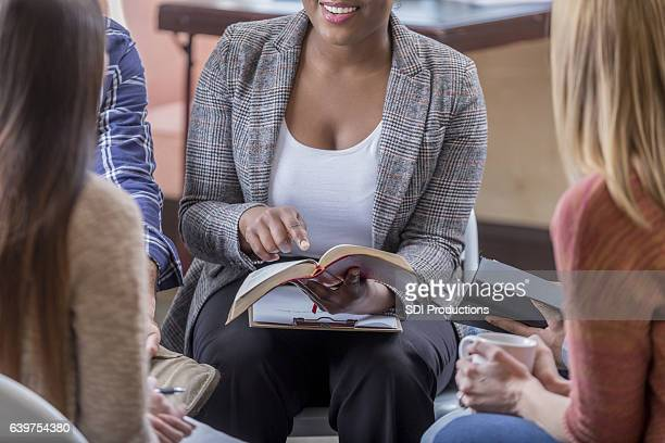 Young woman points to a scripture verse during Bible study