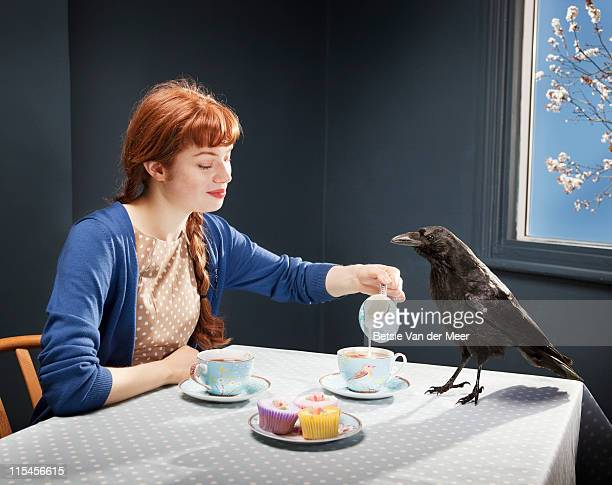 Young woman pooring tea for crow.
