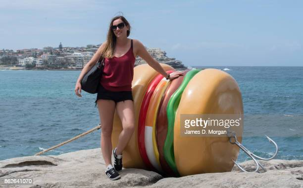 A young woman poses for a phot by 'What a Tasty Looking Burger' by James Dive at Sculpture By The Sea on October 18 2017 in Sydney Australia The...