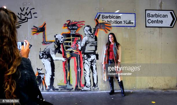 A young woman poses for a photograph in front of street art created in September 2017 near the Barbican Centre in London England by Banksy an...
