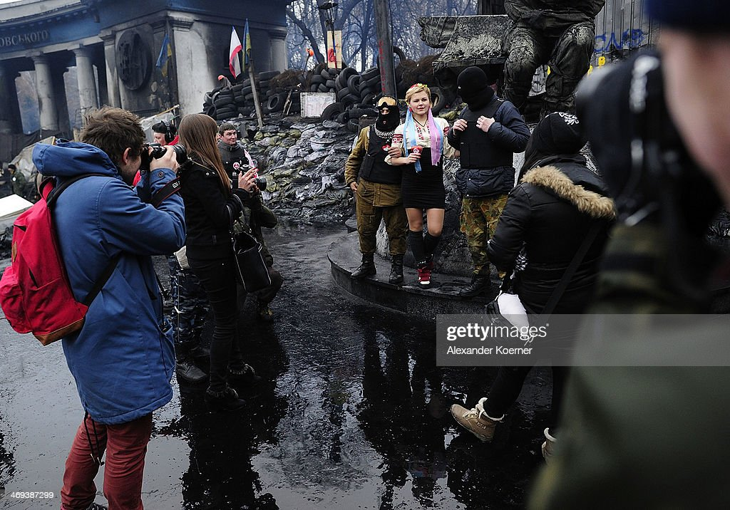 A young woman poses with anti-government protesters inside a barricade on Grushevskogo Street on February 14, 2014, in Kiev, Ukraine. According to Opposition Officals, Berkut police forces could attack the barricades any moment; protesters have gathered inside and prepared fireworks and molotov-cocktails. Media and other people were removed from the barricades. Russian Foreign Minister Sergei Lavrov again issued a warning to the West against interfering in Ukraine's political crisis during today's joint press conference with German federal foreign Minister Walter Steinmeier, who is on a two-day visit to Russia. According to reports Ukrainian opposition leaders Vitaly Klitschko and Arseny Yatsenyuk are set to meet with German Chancellor Angela Merkel on February 18, 2014 in Germany.