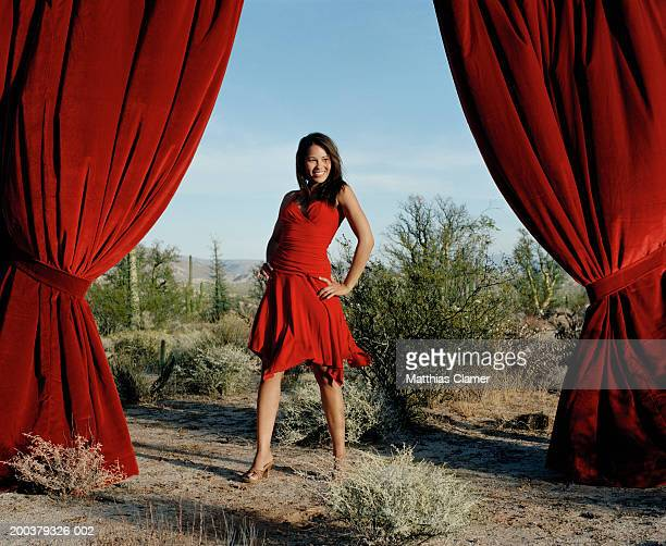 Young woman posing between curtain in desert, smiling