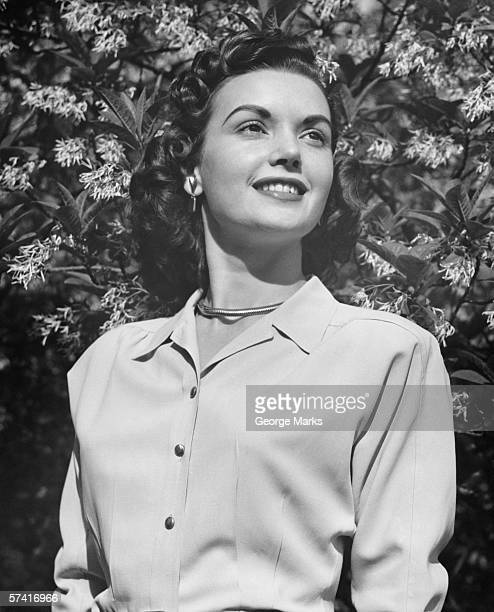Young woman posing by blooming tree, (B&W), (Close-up), (Portrait), (Low angle view)