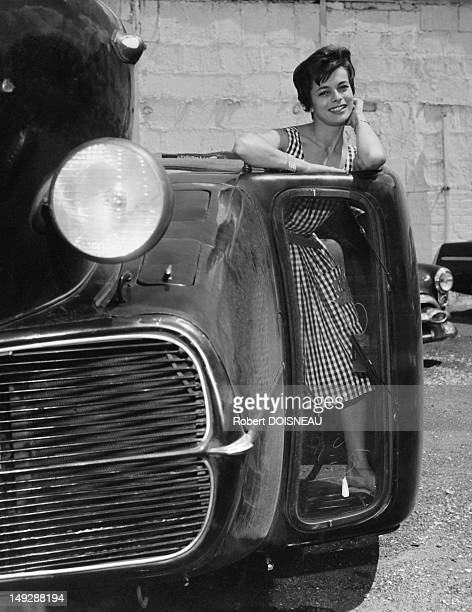 A young woman posing in a car lying on it's side, 1950 in France.