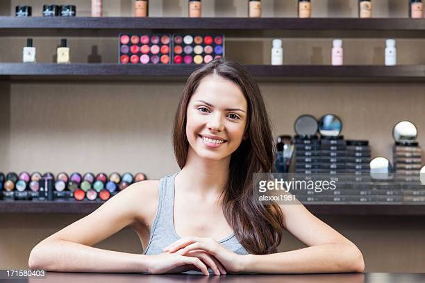 Young woman posing in cosmetic beauty salon, smiling indoors.