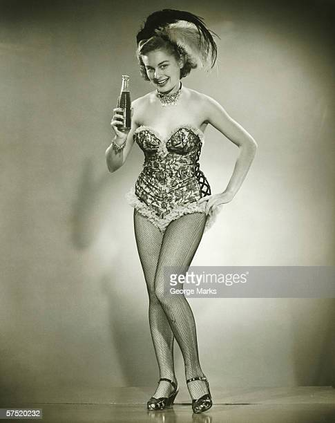 Young woman posing in studio, showing bottle with beverage, (B&W)