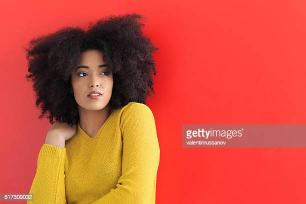 Young woman posing on red background