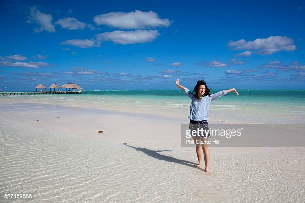 Young woman posing smiling happy i front of aquamarine ultramarine deep blue waters and beach on Cayo Coco island and resorts Ciego de Avila province...