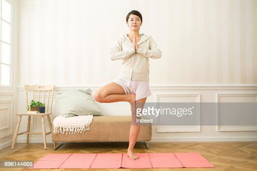 Young woman posing tree pose on mat