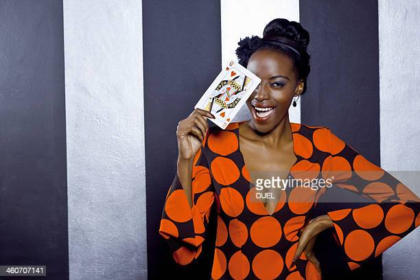 Young woman posing with playing card