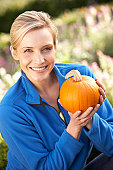 Young woman posing with pumpkin in garden