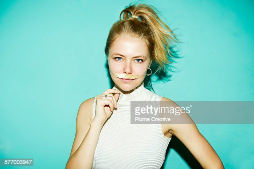 Young woman posing with silly mustache.