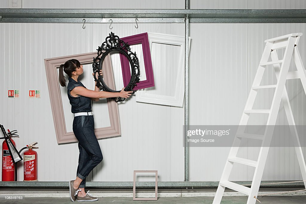 Young woman positioning picture frame : Stock Photo