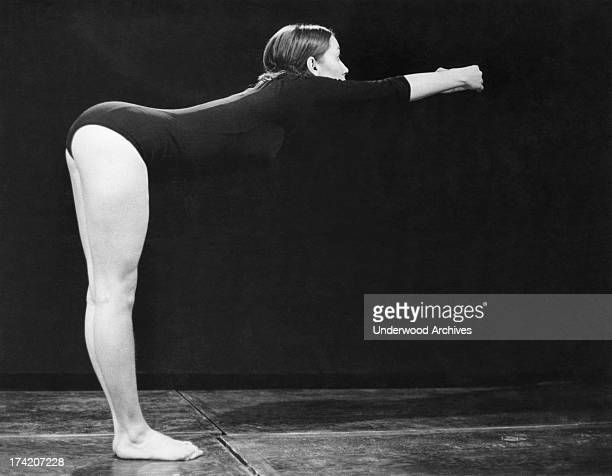 A young woman possibly a gymast and dressed in a leotard leans forward in a stretching stance United States 1960