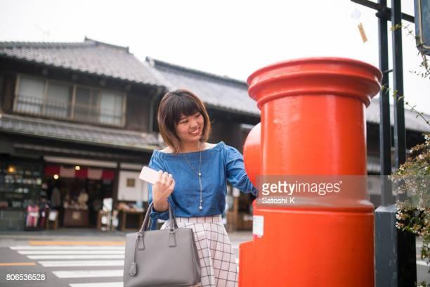 若い女性の伝統的な日本の町でメールを投稿