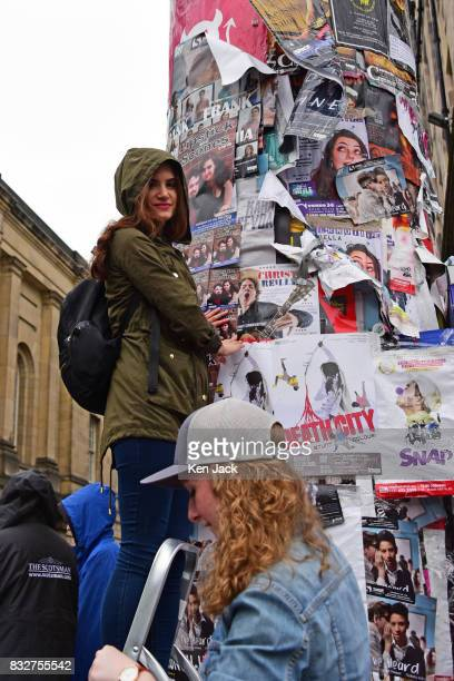 A young woman posts promotional flyers on a pillar during the Edinburgh Festival Fringe on August 16 2017 in Edinburgh Scotland The Fringe is...