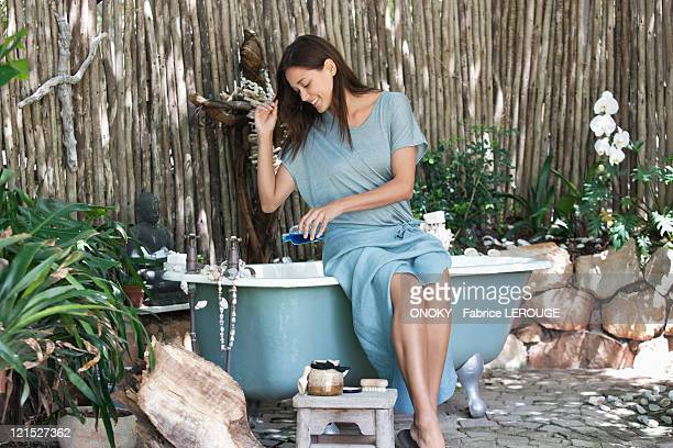 Young woman pouring aromatherapy oil in bathtub