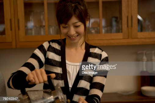 A young woman pouring coffee : Stock Photo
