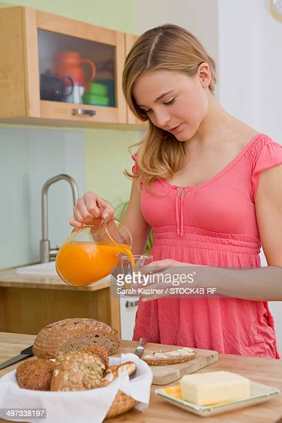 Young woman pouring juice into glass