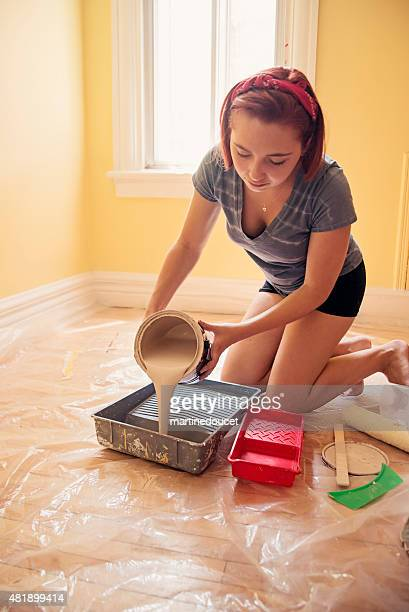 Young woman pouring paint in pans to improve a room.
