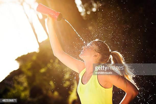Mujer joven vertiendo agua de botella en la cara