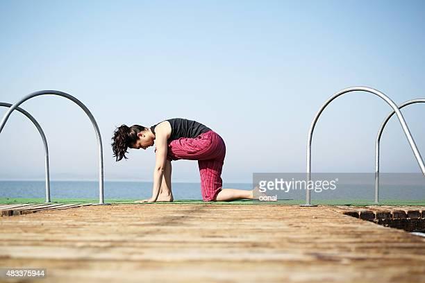 Jeune femme pratiques yoga sur la plage