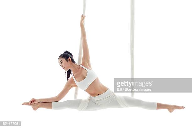 Young woman practicing aerial yoga