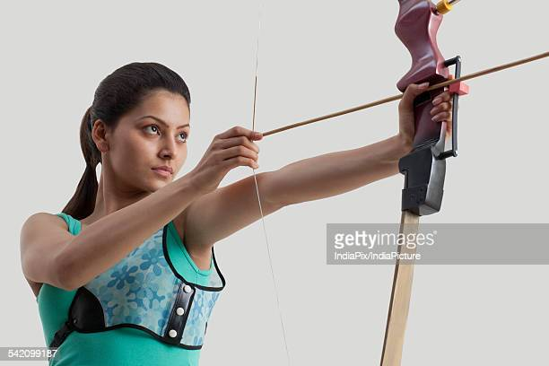 Young woman practicing archery against gray background